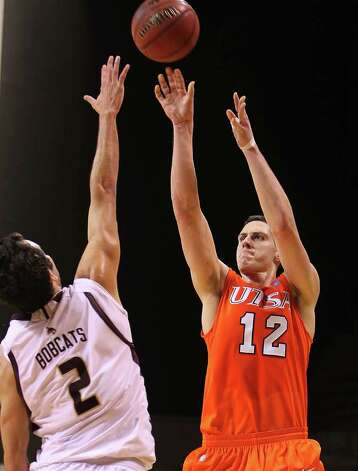 UTSA's Jeromie Hill (12) shoots over Texas State's Brooks Ybarra (02) in men's basketball in San Marcos on Saturday, Jan. 21, 2012. UTSA defeated Texas State, 80-75. Kin Man Hui/San Antonio Express-News Photo: Kin Man Hui, ~ / San Antonio Express-News