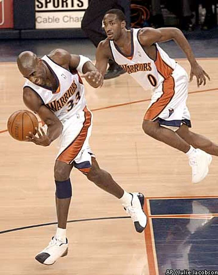 Golden State Warriors' Antawn Jamison, left, takes control of a loose ball as teammate Gilbert Arenas heads downcourt during the first quarter against the Memphis Grizzlies Monday, Feb. 3, 2003, in Oakland, Calif. (AP Photo/Julie Jacobson) Photo: JULIE JACOBSON