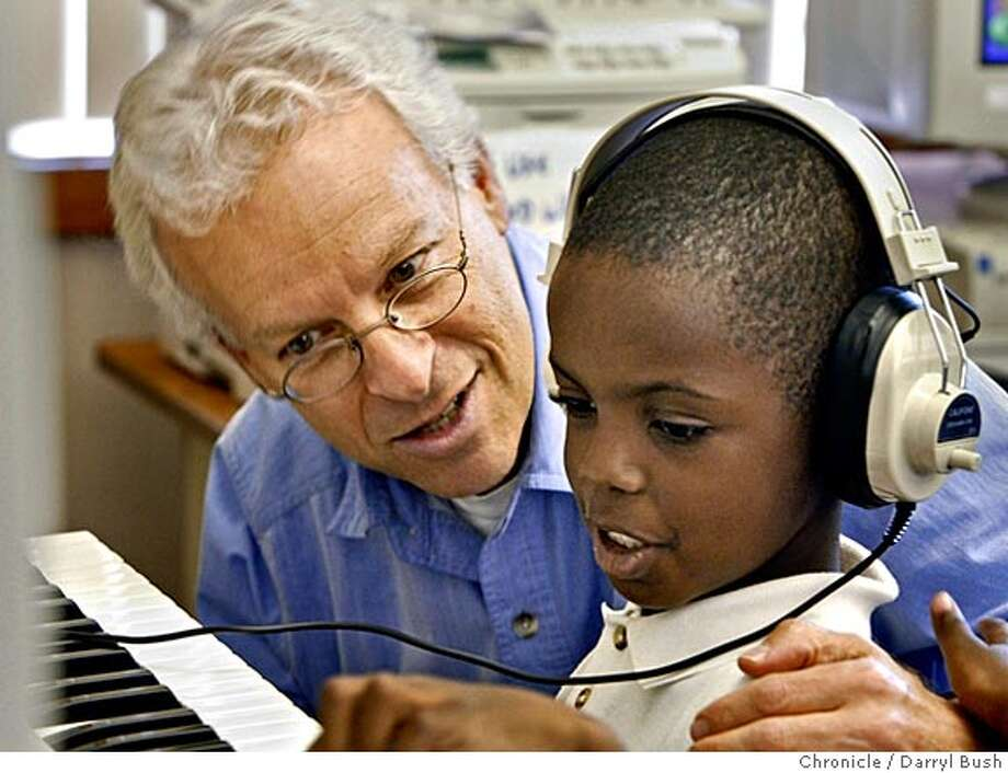 "David Arden, Keys to Achievement Foundation president, gives Donnie White, 7, instruction on using a keyboard and earphones attached to a computer to learn music in ""Keys to Achievement,"" music training in computer lab for Jennifer Banks' kindergarten class at Bayside School. Event on 4/21/05 in Sausalito.  Darryl Bush / The Chronicle Photo: Darryl Bush"