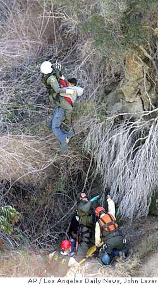 One of two suspected carjackers is hoisted into a waiting Los Angeles County Sheriff's helicopter after being stranded on a ledge in the Angeles National Forest, Wednesday, Nov. 10, 2004, near Sunland, Calif. Two men who allegedly carjacked a vehicle, then lost control of it on a winding mountain road and crashed were rescued Wednesday by firefighters and sheriff's deputies using a helicopter and other equipment. (AP Photo/Los Angeles Daily News, John Lazar) LA TIMES, VENTURA STAR, AV PRESS OUT. NO MAGS Metro#Metro#Chronicle#11/11/2004#ALL#5star##0422460585 Photo: JOHN LAZAR