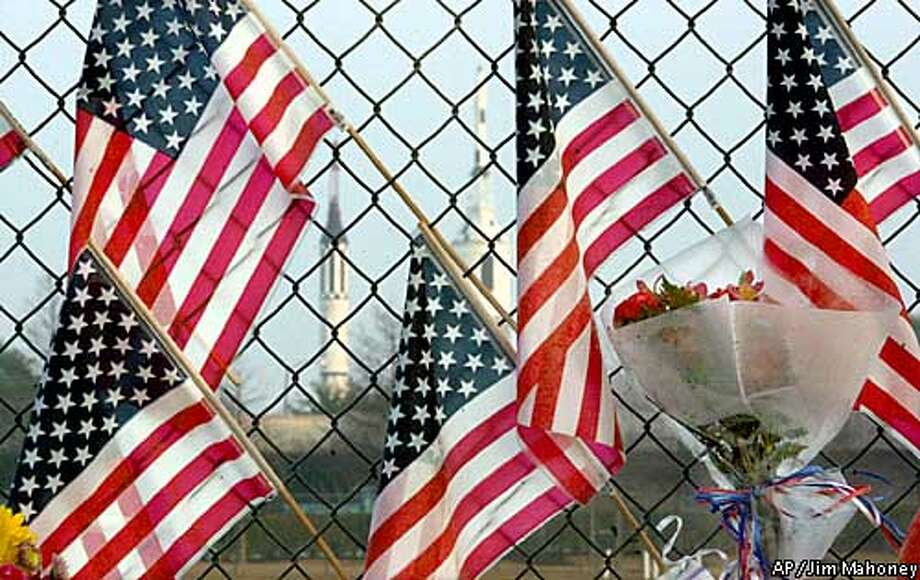 U.S. flags hang on the fence Sunday, Feb. 2, 2003, at the Lyndon B. Johnson Space Center in Clear Lake City, Texas, in honor of the seven astronauts who lost their lives Saturday when the Columbia broke up as the spaceship re-entered Earth's atmosphere. (AP Photo/Dallas Morning News, Jim Mahoney) Photo: JIM MAHONEY