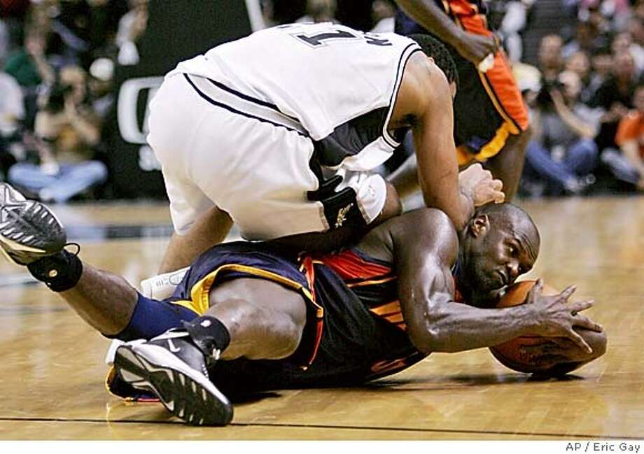 San Antonio Spurs forward Tim Duncan (21) falls on Golden State Warriors center Adonal Foyle (32) as he grabs a loose ball during the second quarter in San Antonio, Wednesday, Nov. 10, 2004. (AP Photo/Eric Gay) Photo: ERIC GAY