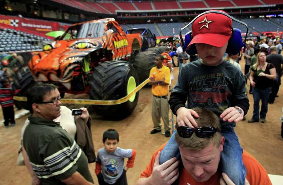 Julian English, 3, of Pearland rides on his father Eric's shoulders next to the monster truck Prowler during the Advanced Auto Parts Monster Jam Pit Party before the monster truck event at Reliant Stadium. Photo: Johnny Hanson, Houston Chronicle / © 2012  Houston Chronicle