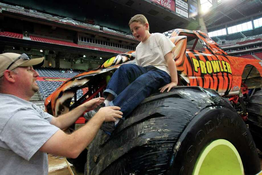 Lane Toutcheque, 11, has his father Larry get him down from sitting on top of the tire on Prowler. More than 4 million monster truck fans attend the Advanced Auto Parts Monster Jam annually. The event will be back in Houston at Reliant Stadium on Saturday, February 4. Photo: Johnny Hanson, Houston Chronicle / © 2012  Houston Chronicle