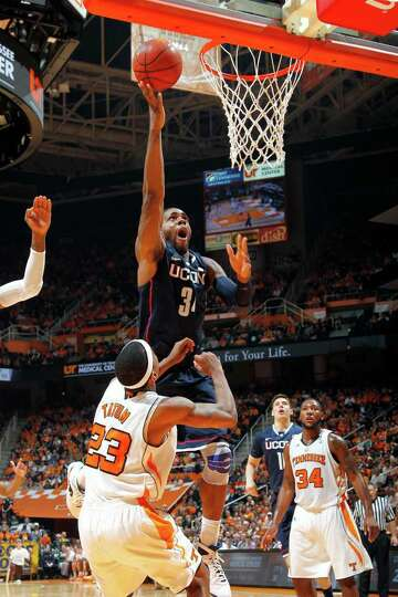 KNOXVILLE, TN - JANUARY 21: Alex Oriakhi #34 of the Connecticut Huskies shoots over Cameron Tatum #2