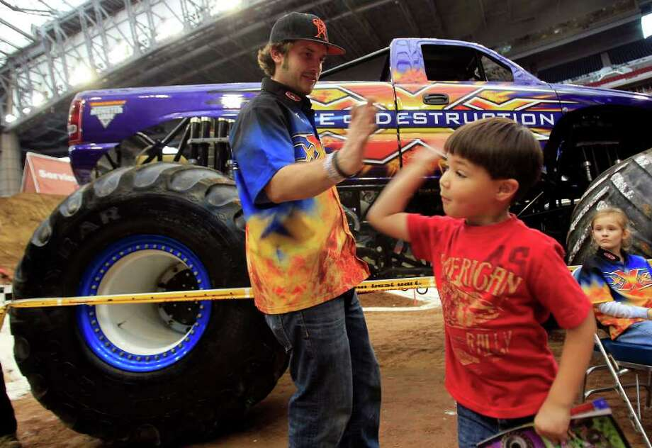 Kylan Adcox, 6, of Baytown, gives State of Destruction monster truck driver Dana Creech a high-five during the Advanced Auto Parts Monster Jam Pit Party. Photo: Johnny Hanson, Houston Chronicle / © 2012  Houston Chronicle