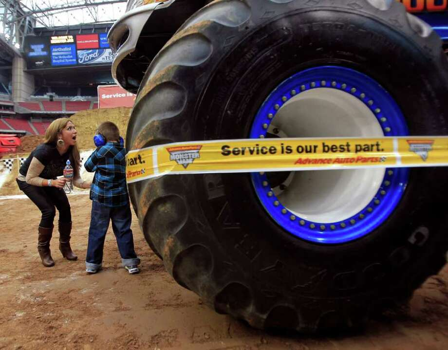 Anthoinette Beal reacts with her son Ashton, 6, while standing next to the West Virginia Mountaineer monster truck. Trucks featured were Grave Digger driven by Charlie Pauken, Superman driven by Sean Duhon, King Krunch driven by David Smith as well as Predator, Pouncer and local radio host Rod Ryan driven by Daron Basl. Photo: Johnny Hanson, Houston Chronicle / © 2012  Houston Chronicle