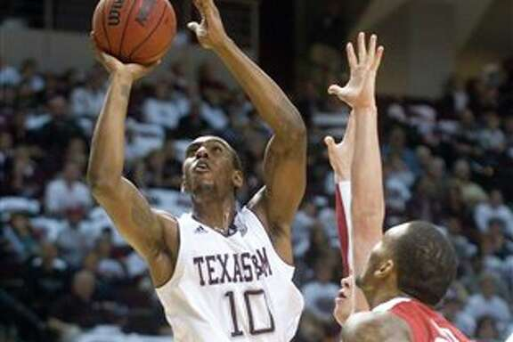 Texas A&M's David Loubeau goes up for the shot in traffic against Oklahoma during the first half of an NCAA college basketball game at Reed Arena in College Station, Texas, Saturday, Jan. 21, 2012. (AP Photo/Bryan-College Station Eagle, Stuart Villanueva)