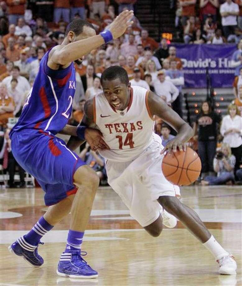 Texas' J'Covan Brown (14) drives past Kansas' Travis Releford, left, during the second half of an NCAA college basketball game, Saturday, Jan. 21, 2012, in Austin, Texas. Kansas won 69-66. (AP Photo/Eric Gay)