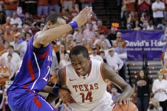 Texas' J'Covan Brown (14) drives past Kansas' Travis Releford, left, during the second half of an NCAA college basketball game, Saturday, Jan. 21, 2012, in Austin, Texas. Kansas won 69-66. (AP Photo/Eric Gay)