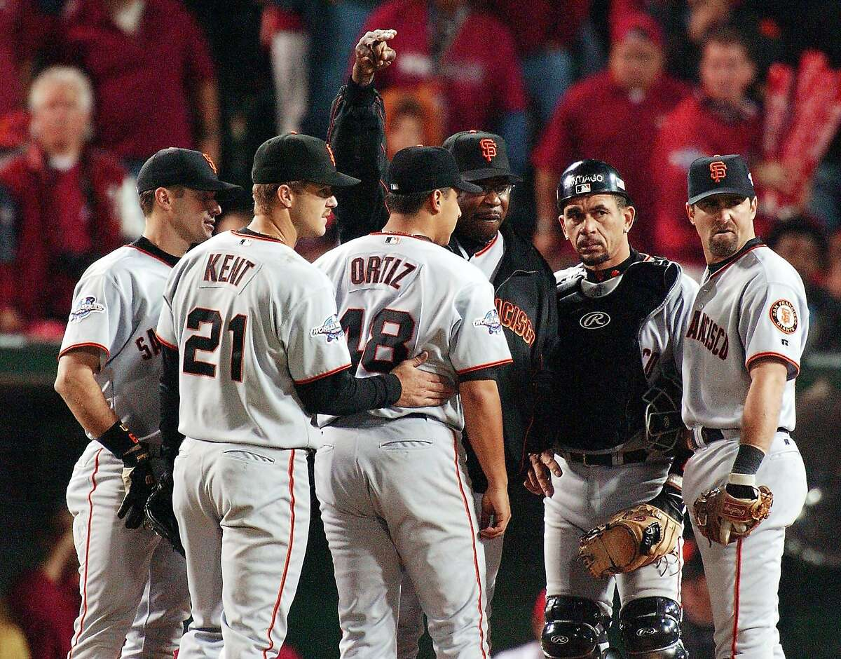 San Francisco Giants manager Dusty Baker signals for a new pitcher as he relieves Russ Ortiz (third from left) in the seventh inning of Game 6 of the World Series in Anaheim, CA, on October 26th, 2002.