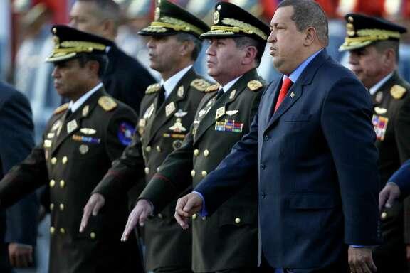 Venezuela's President Hugo Chavez, right, and incoming Defense Minster Gen. Henry Rangel Silva, second from right, arrives to attend Rangel Silva's  swearing-in ceremony at Fort Tiuna military base in Caracas, Venezuela, Tuesday, Jan. 17, 2012. (AP Photo/Fernando Llano)