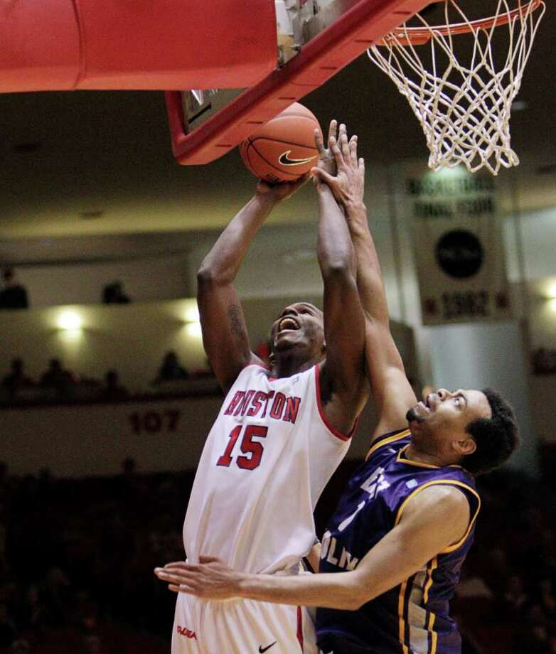 Houston's Leon Gibson (15) drives strong to the basket as he is defended by East Carolina's Darrius Morrow (1) during the first half of a NCAA basketball game between the Houston Cougars and the East Carolina Pirates Saturday, January 21, 2012. Photo: Bob Levey, Houston Chronicle / ©2012 Bob Levey