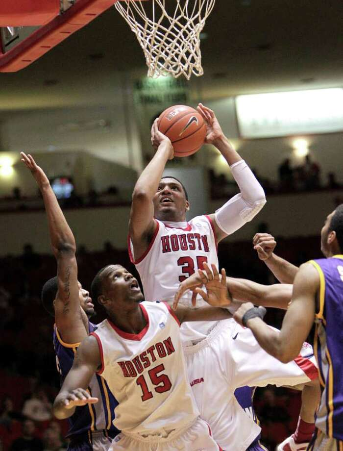 Houston's TaShawn Thomas (35) puts up a shot after grabbing an offensive rebound as teammate Leon Gibson (15) looks on during the first half of a NCAA basketball game between the Houston Cougars and the East Carolina Pirates Saturday, January 21, 2012. Photo: Bob Levey, Houston Chronicle / ©2012 Bob Levey