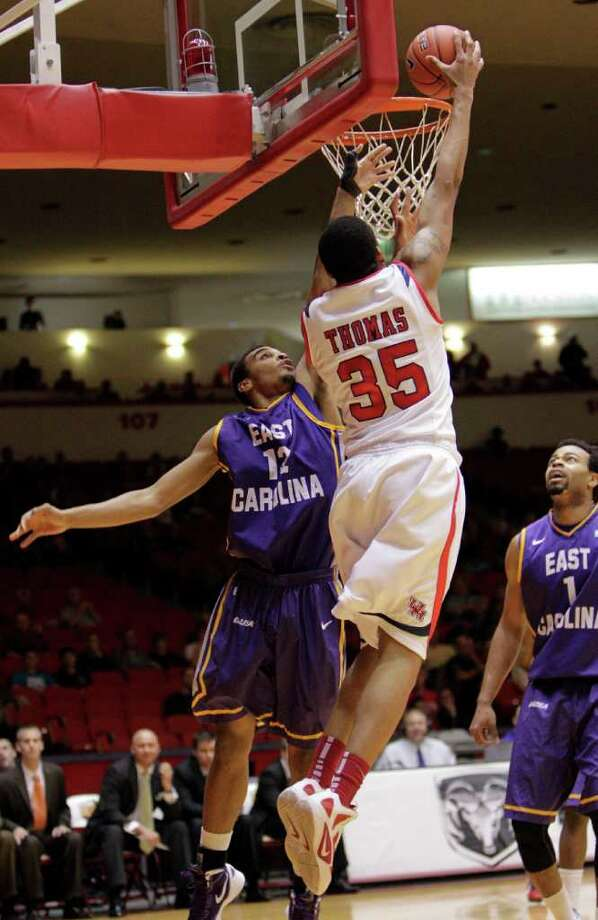 Houston's TaShawn Thomas (35) shoots over East Carolina's Robert Sampson (12) during the first half of a NCAA basketball game between the Houston Cougars and the East Carolina Pirates Saturday, January 21, 2012. Photo: Bob Levey, Houston Chronicle / ©2012 Bob Levey