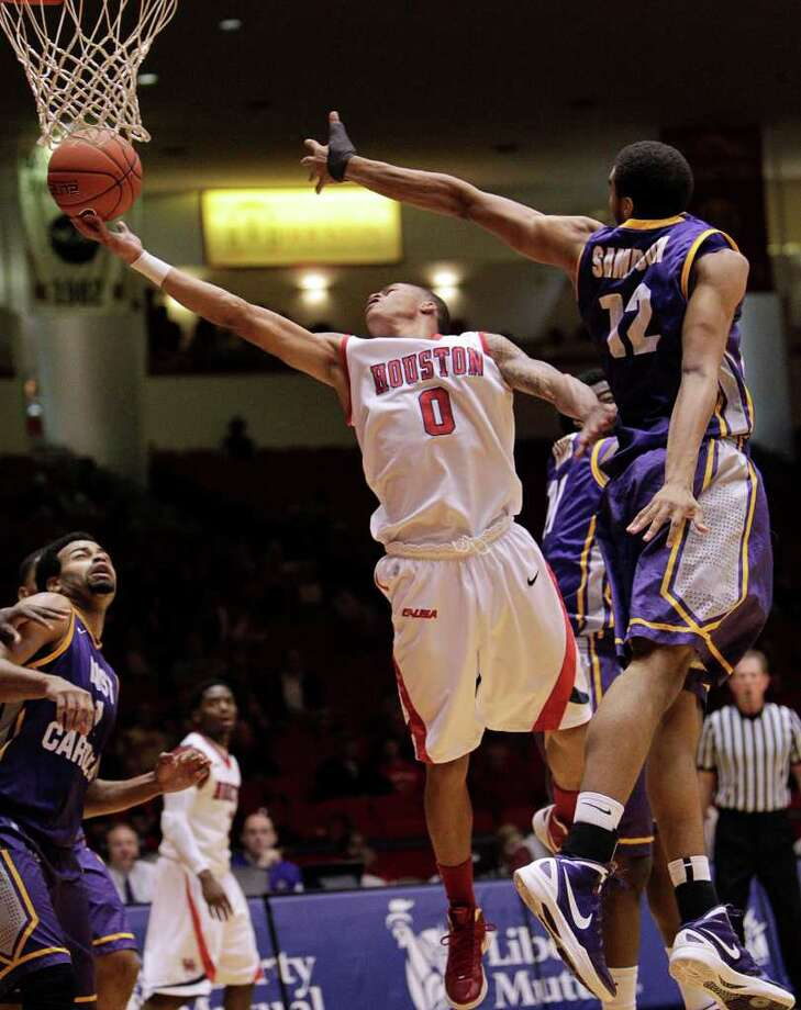 Houston's Jospeh Young (0) drives to the basket for a layup past the outstretched arm of East Carolina's Robert Sampson (12)during the first half of a NCAA basketball game between the Houston Cougars and the East Carolina Pirates Saturday, January 21, 2012. Photo: Bob Levey, Houston Chronicle / ©2012 Bob Levey