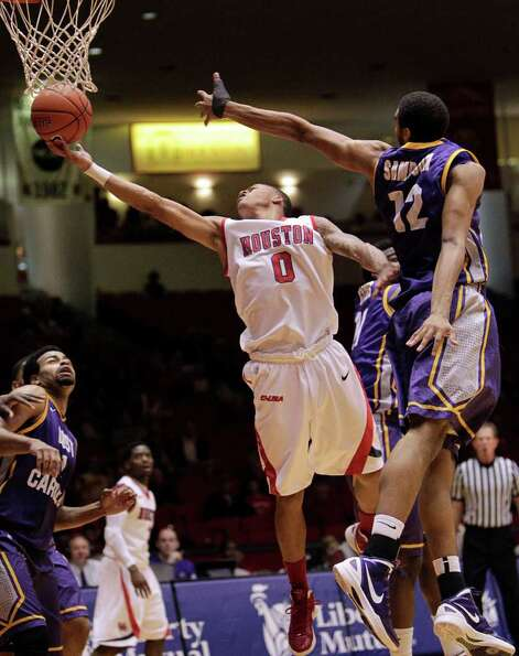 Houston's Jospeh Young (0) drives to the basket for a layup past the outstretched arm of East Caroli