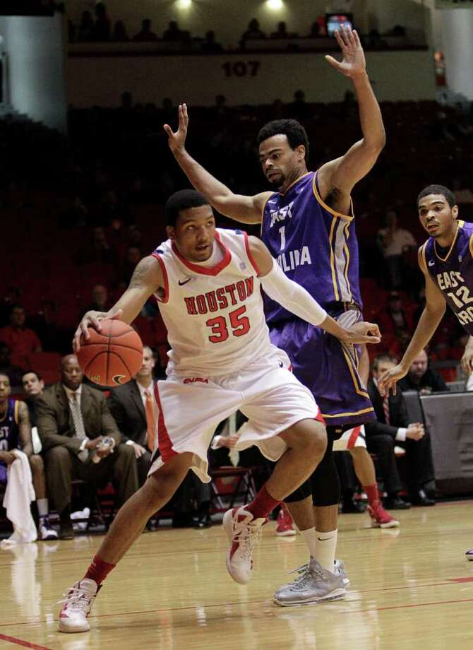 Houston's TaShawn Thomas (35) drives baseline on East Carolina's Darrius Morrow (1) during the first half of a NCAA basketball game between the Houston Cougars and the East Carolina Pirates Saturday, January 21, 2012. Photo: Bob Levey, Houston Chronicle / ©2012 Bob Levey