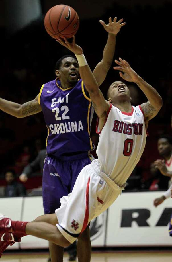 Houston's Jospeh Young (0) takes a hard hit from East Carolina's Paris Roberts-Campbell (22) as drives to the basket during the second half of a NCAA basketball game between the Houston Cougars and the East Carolina Pirates Saturday, January 21, 2012. Houston won 82-76. Photo: Bob Levey, Houston Chronicle / ©2012 Bob Levey