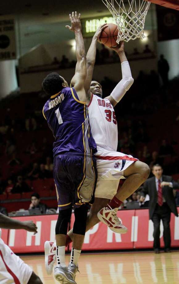 Jan 22: UH 82, East Carolina 76 -Houston's TaShawn Thomas (35) is met by East Carolina's Darrius Morrow (1) as he drives to the basket during the second half. Photo: Bob Levey, Houston Chronicle / ©2012 Bob Levey