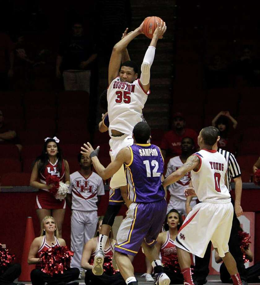 Houston's TaShawn Thomas (35) grabs a big rebound over East Carolina's Robert Sampson (12) in the closing seconds of the game during the second half of a NCAA basketball game between the Houston Cougars and the East Carolina Pirates Saturday, January 21, 2012. Houston won 82-76. Photo: Bob Levey, Houston Chronicle / ©2012 Bob Levey