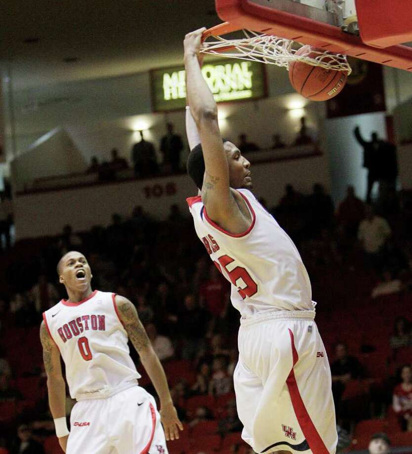 Houston's TaShawn Thomas (35) dunks to put the game away as Jospeh Young (0) reacts during the second half of a NCAA basketball game between the Houston Cougars and the East Carolina Pirates Saturday, January 21, 2012. Houston won 82-76. Photo: Bob Levey, Houston Chronicle / ©2012 Bob Levey