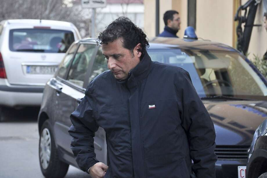 FILE - In this Jan. 14, 2012 photo, Francesco Schettino, captain of the luxury cruiser Costa Concordia, which ran aground off the small Italian island of Isola del Giglio, is arrested in Porto Santo Stefano, Italy. Schettino is under house arrest, facing possible charges of manslaughter, causing a shipwreck and abandoning his ship. A young Moldovan woman who translated evacuation instructions from the bridge after the Costa Concordia ran into the reef, has defended Schettino. (AP Photo/Giacomo Aprili, File) Photo: Giacomo Aprili, Associated Press