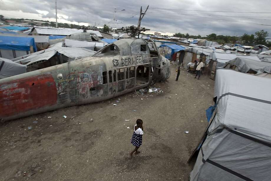ADVANCE FOR USE SUNDAY, JAN. 8, 2012 AND THEREAFTER - In this Jan. 4, 2012 photo, a girl walks past an abandoned helicopter at a camp set up for people displaced by the 2010 earthquake, in what used to be an airstrip in Port-au-Prince, Haiti. Two years afterwards, more than half a million Haitians are still homeless, and many who have homes are worse off than before the Jan. 12, 2010 quake, as recovery bogs down under a political leadership that has been preoccupied with elections and their messy aftermath. (AP Photo/Dieu Nalio Chery) Photo: Dieu Nalio Chery, Associated Press