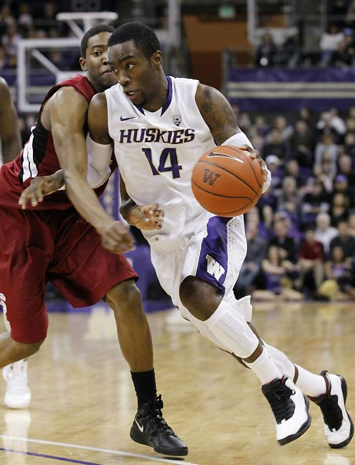 Washington's Tony Wroten (14) drives by Stanford's Chasson Randle in the second half of an NCAA college basketball game on Saturday, Jan. 21, 2012, in Seattle. Washington won 76-63. (AP Photo/Elaine Thompson) Photo: Elaine Thompson, Associated Press