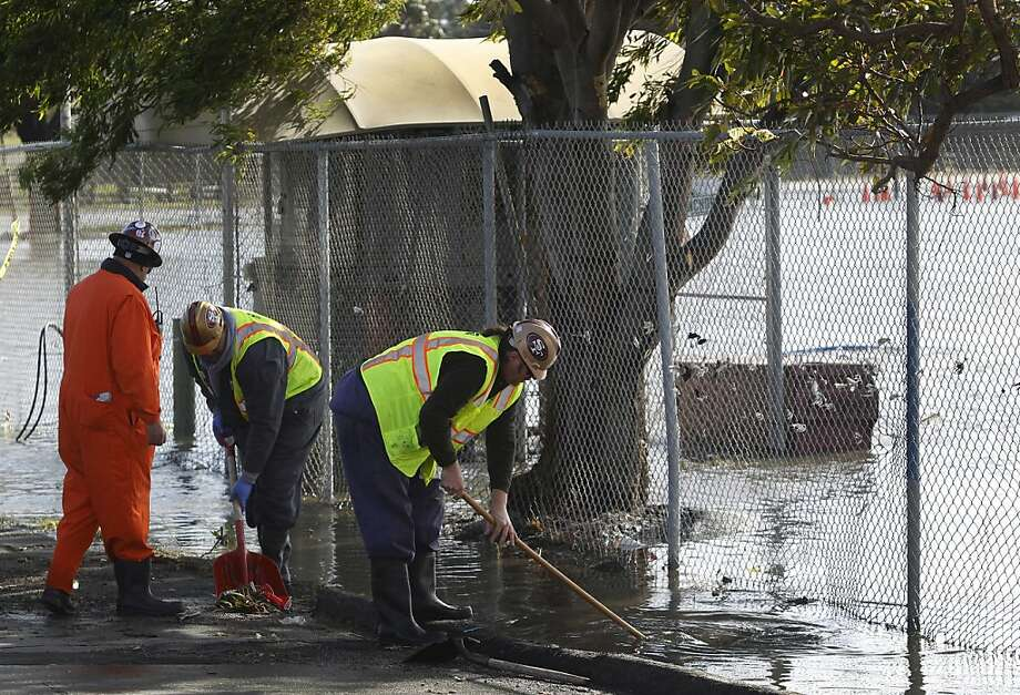 A Public Utilities Commission work crew clears debris after heavy overnight rain flooded the parking lot at Candlestick Park in San Francisco, Calif. on Saturday, Jan. 21, 2012. The crews will remain on site throughout the night and all day Sunday to make sure the lots are accessable by game time. Photo: Paul Chinn, The Chronicle