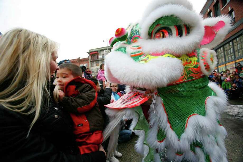 A lion scares a child during a traditional Chinese Lion Dance outside the Wing Luke Museum on Saturday, Jan. 21, 2012. The Lieu Quan Lion Dance Team blessed the Wing Luke Museum in the International District to rid it of any bad luck for 2012, the lucky year of the Dragon. The Lunar New Year, or Chinese New Year, is one of the most important traditional Chinese Holidays. Photo: LINDSEY WASSON / SEATTLEPI.COM
