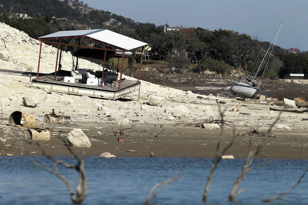 A sailboat lists on its side on the ground next to a beached dock Thursday January 19, 2012 as water levels at Medina Lake continue to plummet. The lake is 52 feet below pool and is expected to continue to drop as long as the long term forecast calls for below average rainfall. Because the lake is so low, farmers will only be able to draw water in March and April. John Davenport/San Antonio Express-News Photo: JOHN DAVENPORT, SAN ANTONIO EXPRESS-NEWS / SAN ANTONIO EXPRESS-NEWS (Photo can be sold to the public)
