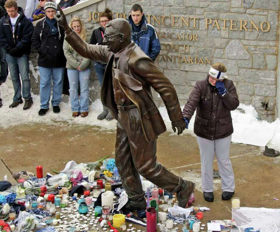 A woman pays her respects at a statue of Joe Paterno outside Beaver Stadium on the Penn State University campus after learning of his death Sunday, Jan. 22, 2012 in State College, Pa. Photo: AP