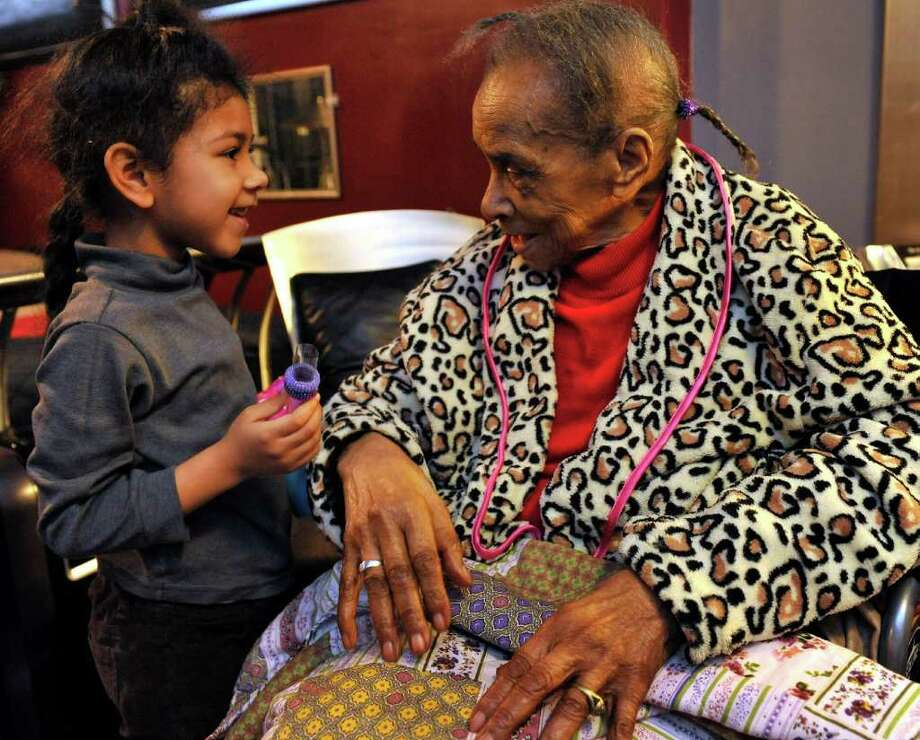 Texana Hollis, 101,  talks to her friend Pollian Cheeks' granddaughter Jahzara. Hollis is living with Cheeks after being evicted. Photo: Associated Press, John T. Greilick