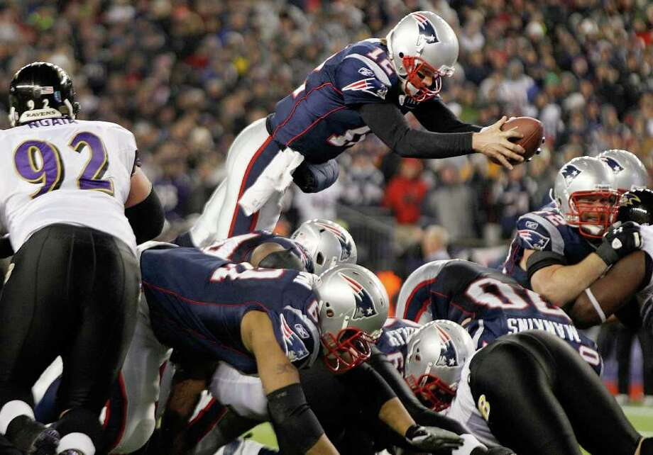 Patriots quarterback Tom Brady, who was held without a TD pass, dives for a 1-yard touchdown during the fourth quarter. Photo: AP