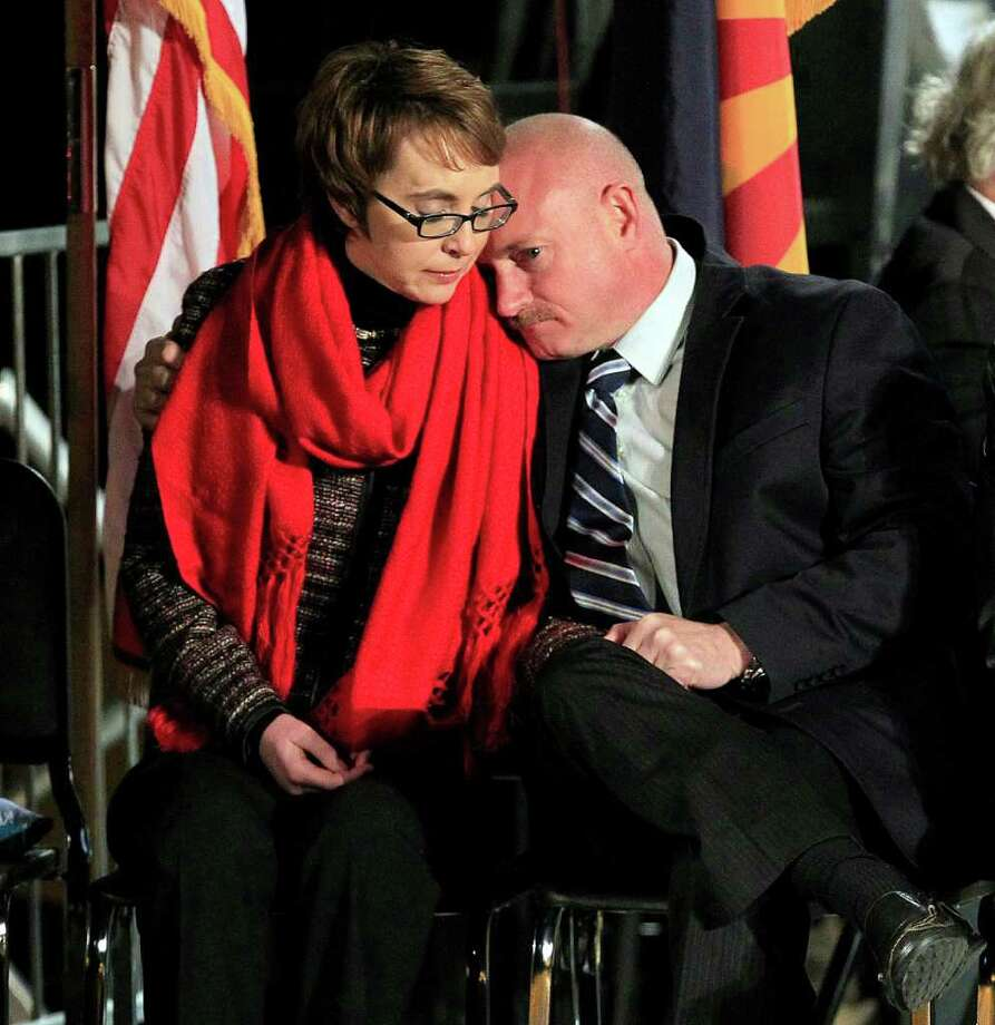 Mark Kelly leans on the shoulder of his wife, U.S. Rep. Gabrielle Giffords, at a memorial vigil remembering the victims and survivors of the shooting that wounded Giffords, 12 others and killed six one year ago Sunday, Jan. 8, 2012, in Tucson, Ariz. Photo: AP