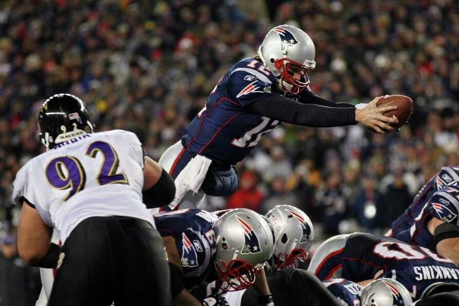 FOXBORO, MA - JANUARY 22:  Tom Brady #12 of the New England Patriots dives into the end zone to scor