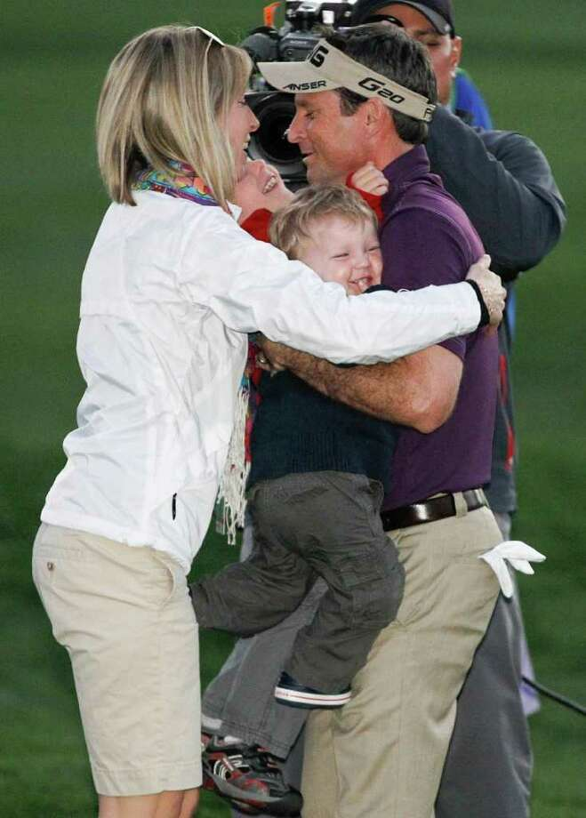 Mark Wilson hugs his wife, Amy, and children after winning the Humana Challenge. Photo: AP
