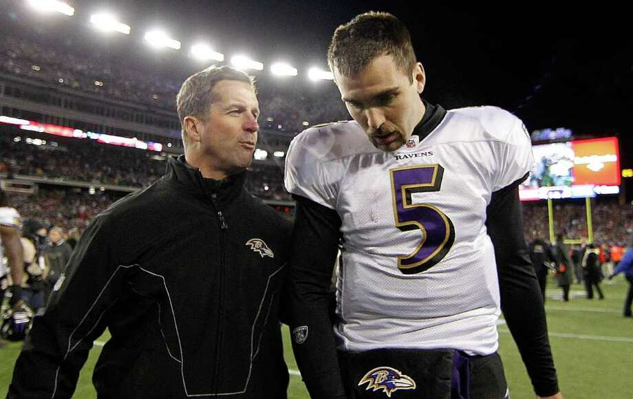 Ravens coach John Harbaugh leaves the field with QB Joe Flacco, who threw for 306 yards and two touchdowns. Photo: AP
