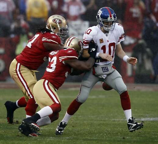 NaVorro Bowman, left, and Ray MacDonald, get to Eli Manning and knock the ball loose for a fumble in the first quarter. New York recovered the ball. The San Francisco 49ers played the New York Giants in the NFC Championship game at Candlestick Park in San Francisco, Calif., on Sunday, January 22, 2012. Photo: Brant Ward, The Chronicle