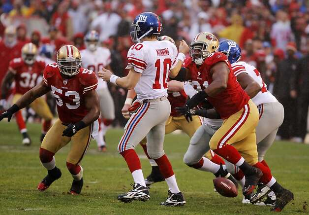 The 49ers' Ray McdDonald, right, forces a fumble by the Giants' Eli Manning during the first quarter of Sunday's game. The San Francisco 49ers played the New York Giants in the NFC Championship game at Candlestick Park in San Francisco, Calif., on Sunday, January 22, 2012. Photo: John Storey, Special To The Chronicle