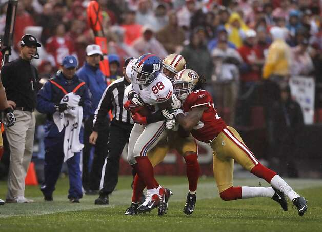 The Giants' Hakeem Nicks is brought down by the 49ers' Chris Culliver (behind) and Dashon Goldson (right) after a successful catch for 1st down in the 1st quarter of Sunday's game. The San Francisco 49ers played the New York Giants in the NFC Championship game at Candlestick Park in San Francisco, Calif., on Sunday, January 22, 2012. Photo: Paul Chinn, The Chronicle