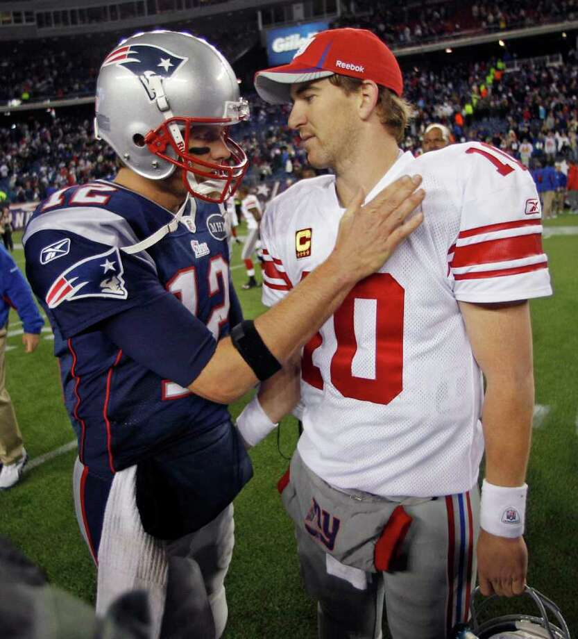 Giants QB Eli Manning (right) is congratulated by his Patriots rival, Tom Brady, after New York's 24-20 victory Nov. 6. Photo: AP