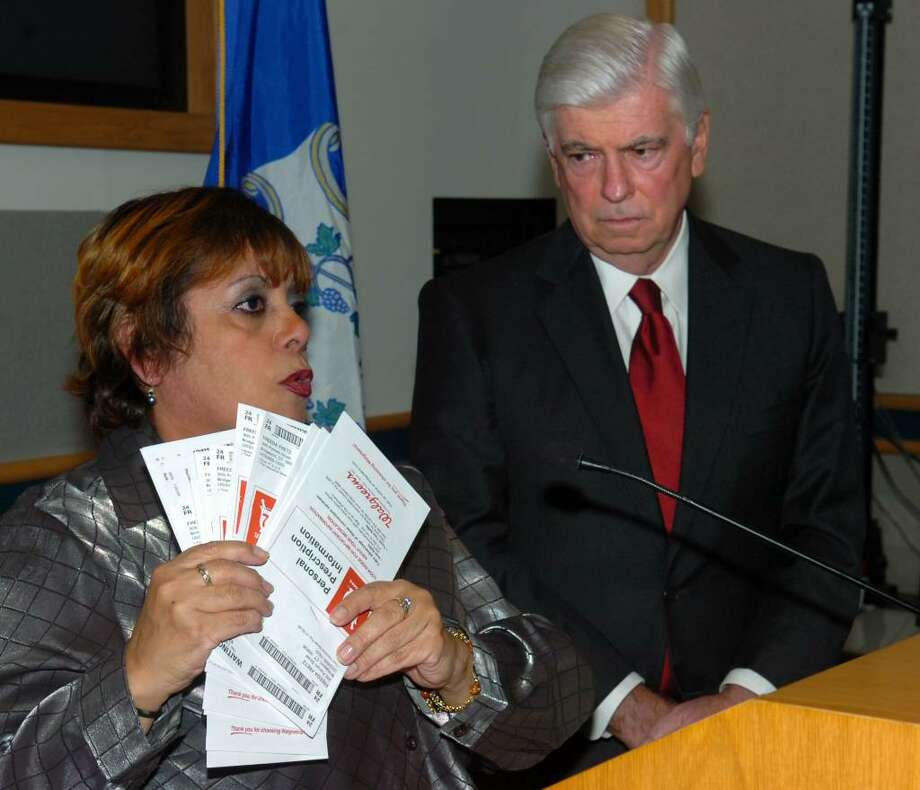 Sen. Christopher Dodd listens as Freeda Fretz, of Bridgeport, talks about her struggles with health care costs during a forum on health care reform legislation, held at Bridgeport Hospital, in Bridgeport, Conn. on Friday, Oct. 30th, 2009. Fretz, a cancer survivor, holds receipts for just a month's worth of medicine that she has paid for to treat her chronic asthma. Photo: Ned Gerard / Connecticut Post