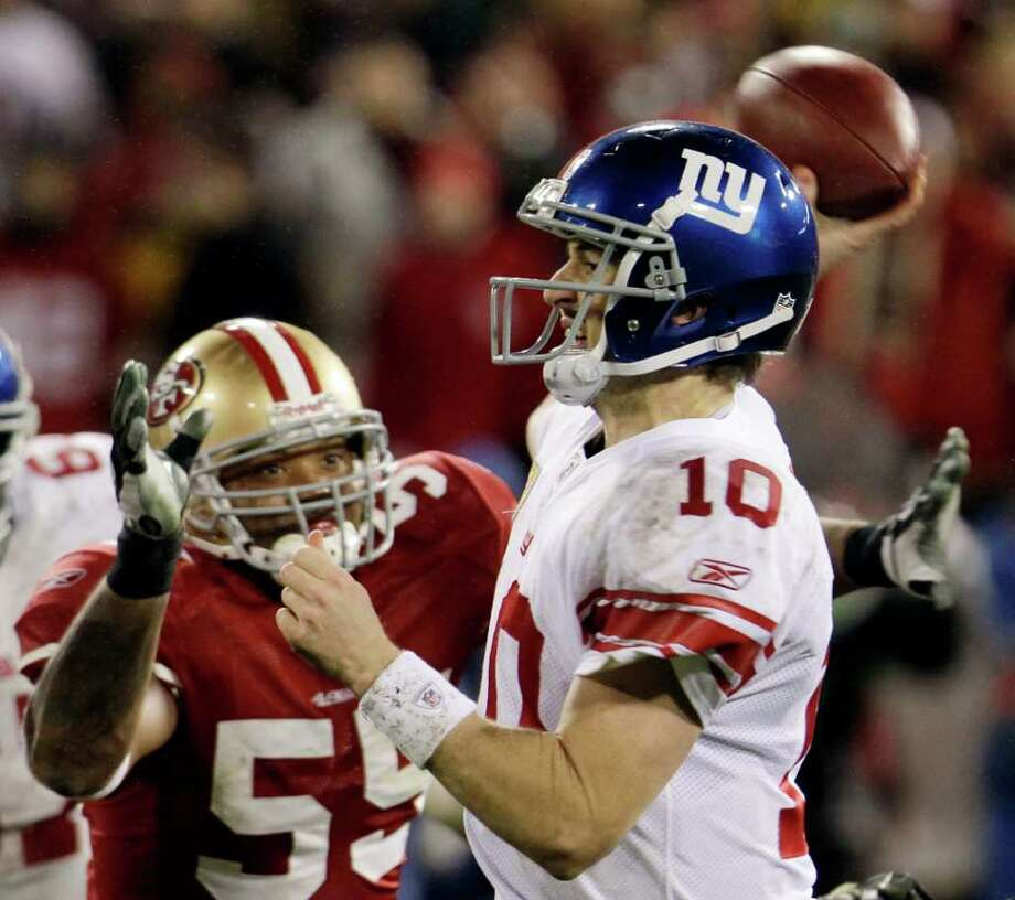 New York Giants' Eli Manning throws while being pressured by San Francisco 49ers' Ahmad Brooks (55) during the second half of the NFC Championship NFL football game Sunday, Jan. 22, 2012, in San Francisco. Photo: Paul Sakuma