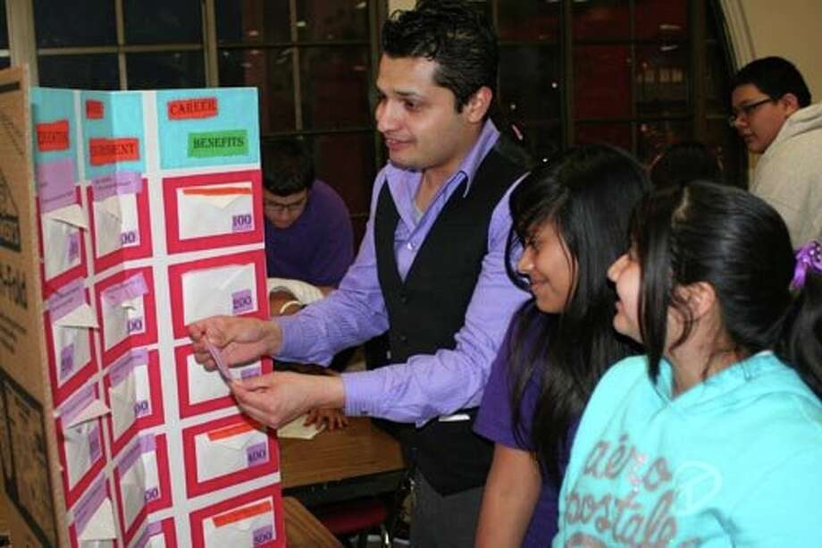 """Ashley Fierra and Tiffani Vargas, seventh-graders in the San Antonio Independent School District, and their teacher, Earnest Guerrero, go over """"jeopardy"""" -questions about a career as a doctor during a school event Jan. 12. Courtesy photo Photo: Courtesy Photo"""