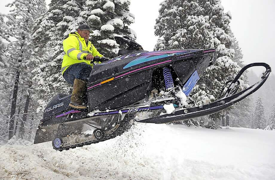 In this Saturday, Jan. 21, 2012, photo, Richard Foster gets some air on his snowmobile in La Porte, Calif., after Friday's snowfall.  (AP Photo/Appeal-Democrat, Nate Chute) Photo: Nate Chute, Associated Press