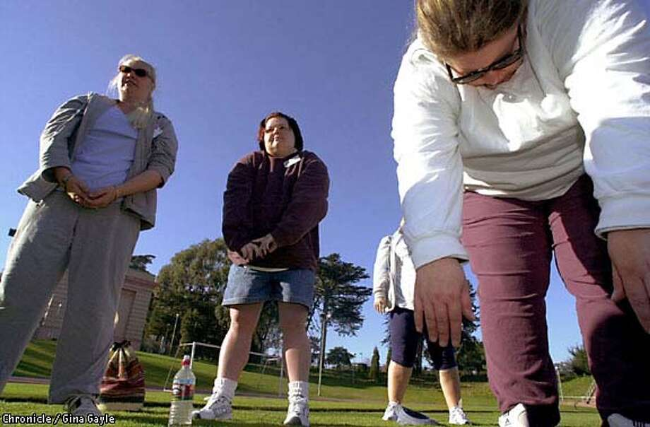 Warming up: Kerry Harvey of San Pablo, Rian Schmidt of Pleasanton and Michelle May of Oakland stretch at Kezar Stadium during their first day of training for Bay to Breakers. Chronicle photo by Gina Gayle