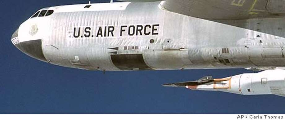 NASA's B-52 mother ship carries the X-43A, perched atop its booster rocket, lower right, on a captive carry flight Jan. 26, 2004. NASA said Wednesday, March 24, 2004, the X-43A is scheduled to make a brief flight on Saturday during which the space agency hopes it will reach Mach 7, or nearly 5,000 mph. The first attempt to to fly the jet three years ago resulted in a an explosion over the Pacific Ocean. (AP Photo/NASA Dryden Flight Research Center, Carla Thomas) HANDOUT JAN 26 2004 PHOTO NASA's B-52 mother ship, above, carries the X-43A booster rocket, at left, on a captive carry flight in January of this year. The X-43A is scheduled to make a brief flight today in an attempt to reach Mach 7, or 5,000 mph. ProductNameChronicle #######0421691838 Nation#MainNews#Chronicle#11/10/2004#ALL#5star##0421691838 Photo: CARLA THOMAS