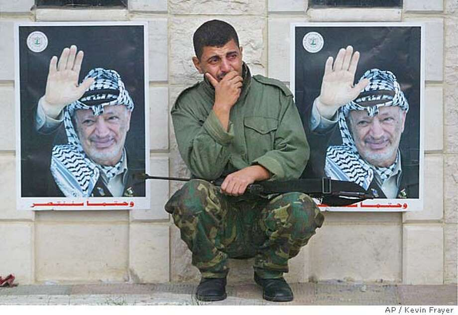 A soldier from Palestinian leader Yasser Arafat's 17th Force Presidential Guard weeps outside his former headquarters in Gaza City, Thursday, Nov. 11, 2004, after hearing of his death in Paris. (AP Photo/Kevin Frayer) Foreign#MainNews#Chronicle#11/11/2004#ALL#5star-dot#a19#0422461248 Photo: KEVIN FRAYER